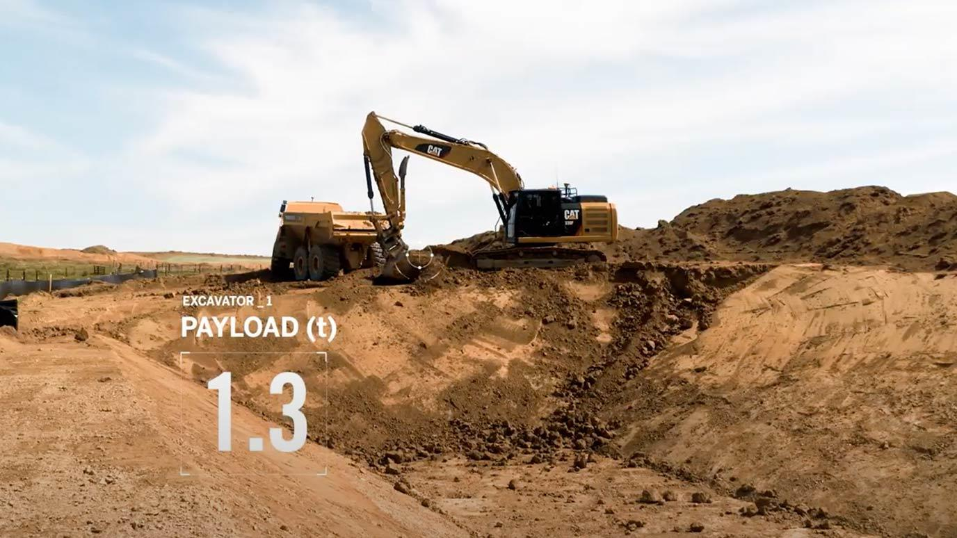 Excavator loading a truck with payload data displayed